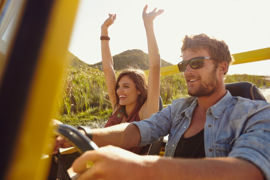 Happy couple enjoying on a long drive in a car. Friends going on road trip on summer day. Caucasian young man driving a car and joyful woman with her arms raised. ** Note: Shallow depth of field